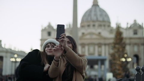 Two excited Italian friends looking out at St Peter's Basilica in St Peter's Square in the Vatican taking pictures together with soft natural lighting. Medium shot on 4k RED camera.