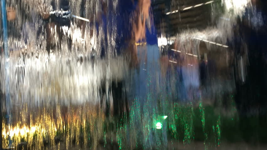Curtain waterfalls.view from inside waterfall or rain falling at the walkway and human walking in blurred background. | Shutterstock HD Video #1022637967