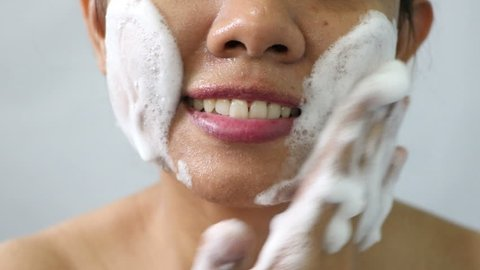 Close up Asian woman washing face by make bubble facial foam and cleansing her face skin