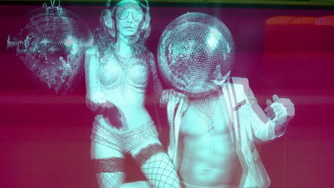 stunning disco woman in silver costume and her male partner with a mirror ball for a head