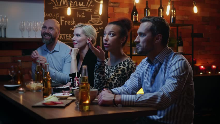 Group of friends wathching tv in a cafe behind bar counter | Shutterstock HD Video #1022687467