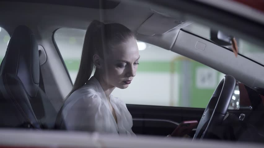 Young stylish looking caucasian woman with pony tail dressed in white shirt sits in car and holds steering wheel with both hands next to underground parking lot.