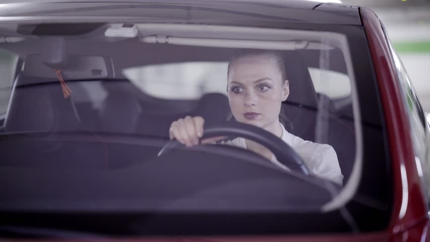 Cute young blonde girl with pony tail wearing white classic shirt sitting in red car behind steering wheel and looking around in underground garage.