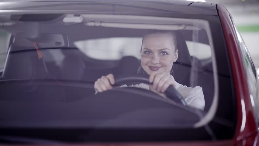 View of cute young woman with pony tail dressed in white classic shirt sitting in red car behind steering wheel when it's starts smoking outside in underground garage.