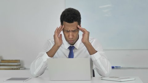 Stressed Afro-American Businessman with Headache Working on Laptop