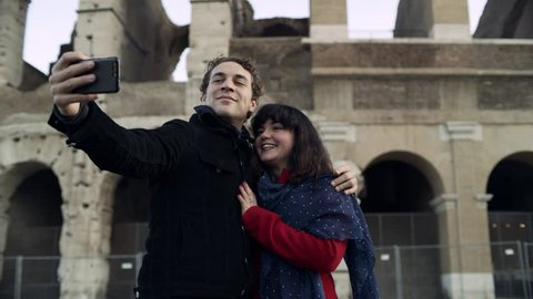 On a beautiful sunny day, a happy, loving Italian couple take pictures on a phone together in front of the Coliseum in Rome. Medium shot on 4k RED camera.