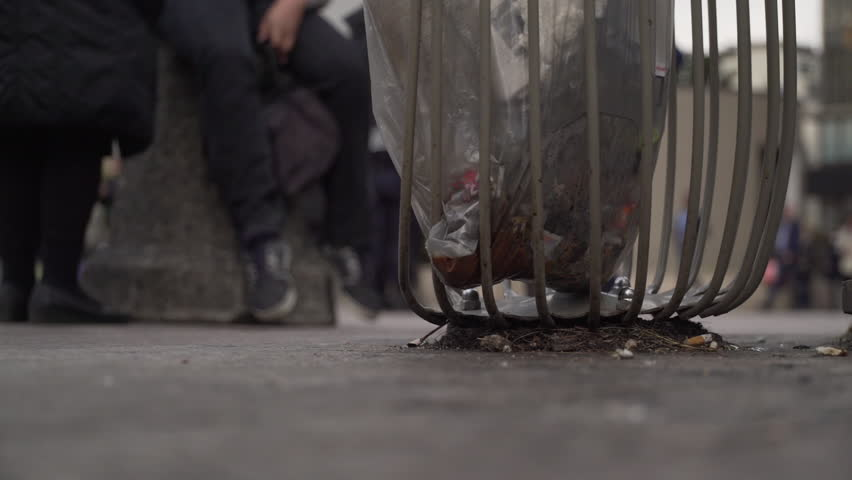 Close up shot of a bin full of trash with people walking behind in Paris, France | Shutterstock HD Video #1022819467