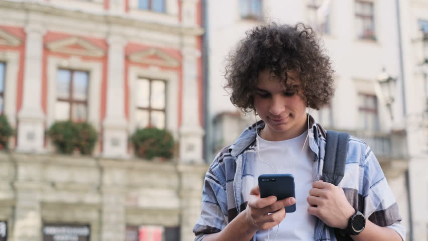 Blogger in headphones using smartphone, listening to music and browsing on smartphone. Outdoor, portrait. Man scrolls through social media on device, reading news on app | Shutterstock HD Video #1022844907