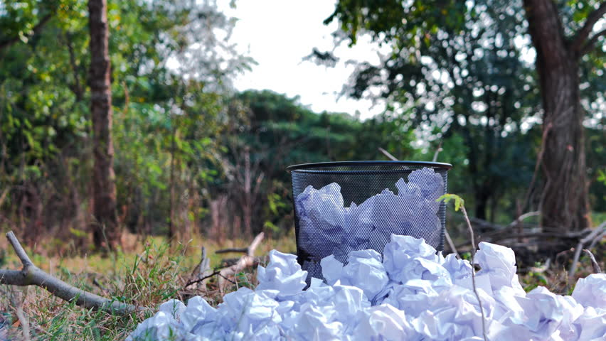 Thrown paper to metal basket bin in the jungle. recycle, Saving resources nature and environment concept. Slow Motion | Shutterstock HD Video #1022861917