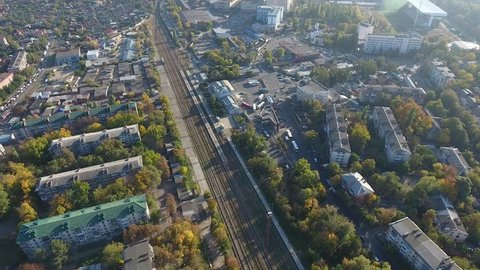 Aerial view: railway station Krasnodar-2 in the city center, among the sleeping area and residential buildings, railway in city Krasnodar Russia. Top view from above train 4k.
