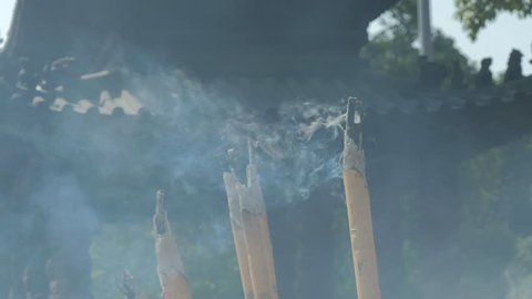 Incense sticks are burning slowly in the burner of a chinese temple. Close focus of incense with copy space for text or advertising.