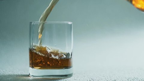 Whiskey or brandy Poured Into Glass on a white background