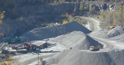Yellow dump truck in a quarry, extraction of a stone in a quarry, yellow loaded dump truck rides in a quarry, working process in a quarry