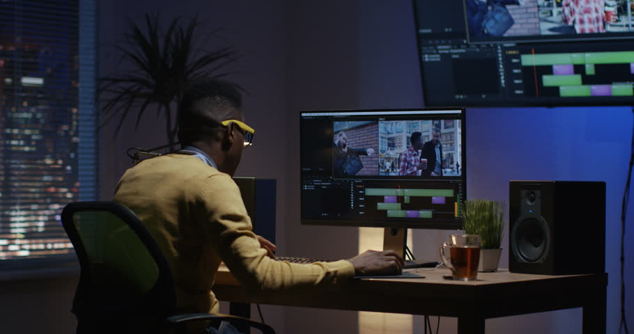 Medium shot of a young man sitting back and editing a video inside a modern video studio | Shutterstock HD Video #1022891107