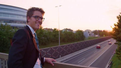PORTRAIT, SUN FLARE, SLOW MOTION: Successful Caucasian yuppie turns around while watching the sunset above the highway. Young businessman smiles while standing above the busy freeway running past city