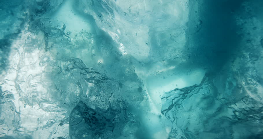 Underwater ice with rising water bubbles. Macro shot of beautiful blue underwater ice.