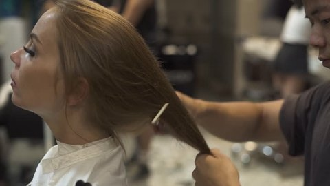Man hairstylist combing dry woman hair in barbershop. Woman in beauty salon. Hairdresser brushing long hair young woman for hairstyling. Hairstyle and beauty concept