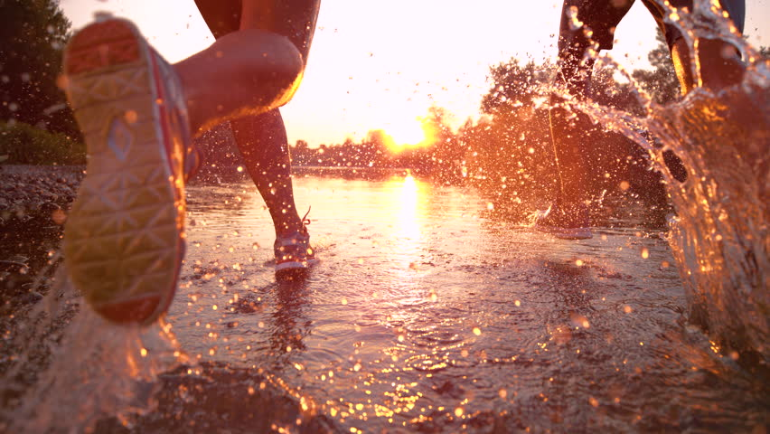 SLOW MOTION TIME WARP, SUN FLARE, CLOSE UP: Fit training partners run in refreshing river water towards beautiful summer sunset. Glassy drops of water fly as young couple jogs through serene nature. #1022986537