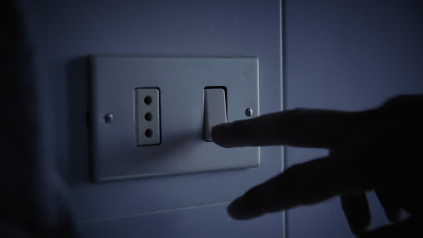 A hand turning the light switch on and off. Int. day, detail close-up shot.