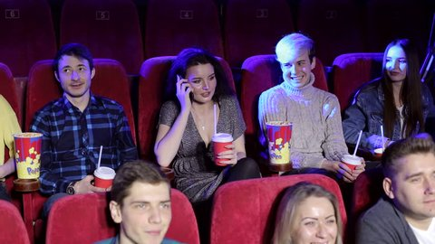 Rude woman talking on phone and disturbing other viewers in cinema. Woman in the theater talking on a cell phone and watch a movie, she disturbing and the man makes her remark.