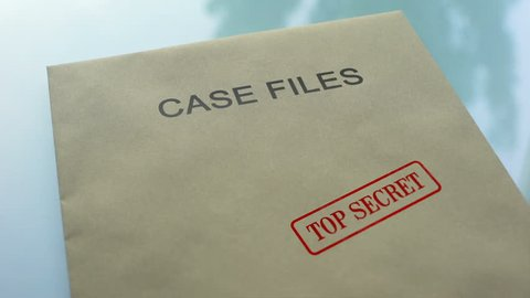 Case files top secret, hand stamping seal on folder with important documents
