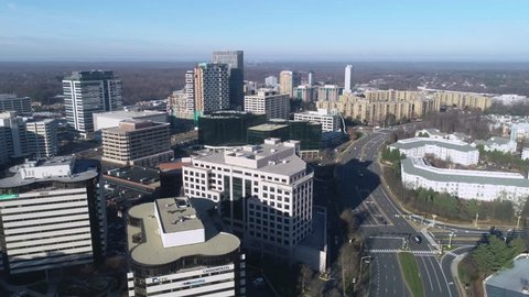 Tysons, VA / USA - December 27 2018: Slow descent while panning right to left across the Tysons Corner skyline in the morning from International Drive.