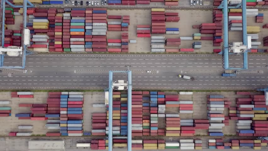 Transtainer dock - Various brands and colours of Shipping containers stacked by Transtainers (Mobile gantry cranes) off of service trucks - Top down aerial footage. | Shutterstock HD Video #1023116647