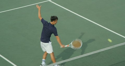 A Tennis Player runs across court to make the shot and gets ready for the return in slow motion.