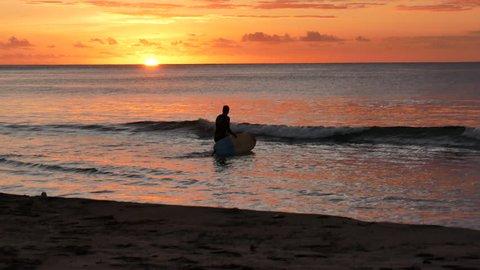 Tamarin Bay, West Coast / Mauritius - 09 01 2018: Surfer on surfboard paddling over waves near the beach during a tropical sunset Tamarin Bay Mauritius