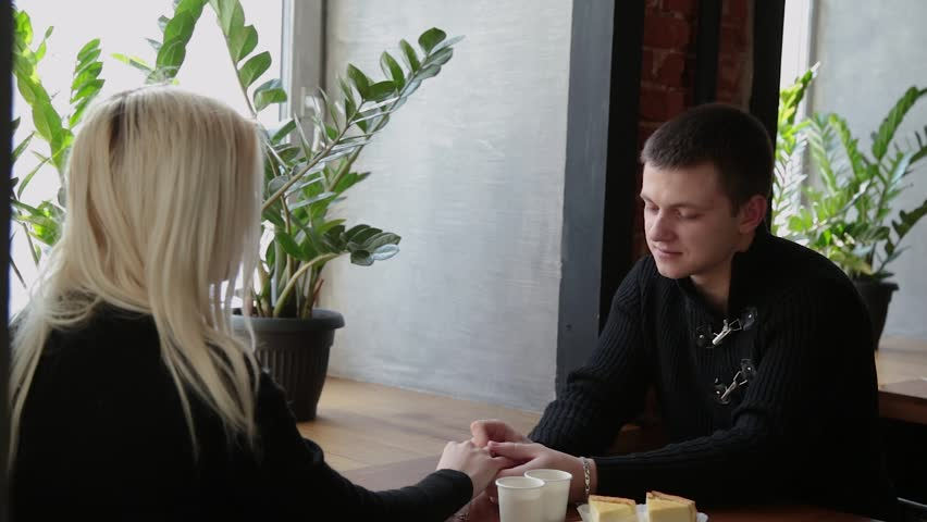 Love couple sitting in a cafe talking and looking at each other. | Shutterstock HD Video #1023165577