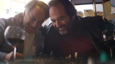 Mature men enjoying a game of chess and a glass of wine together