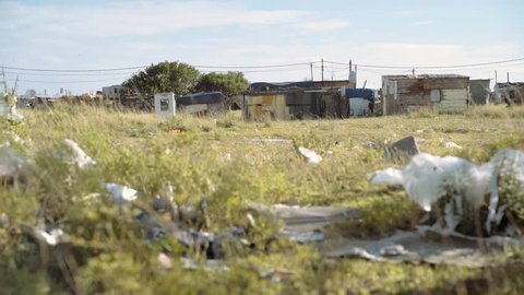 Garbage and plastic litter ourside an impoverished shanty town of tin shacks. South Africa.