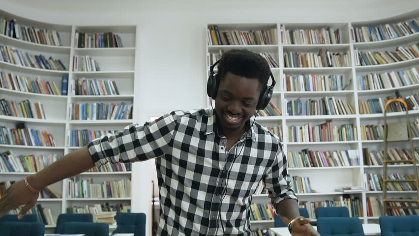 Portrait shot of young african male student in the shirt dancing in the white modern library while listening music in the headphone. | Shutterstock HD Video #1023174037