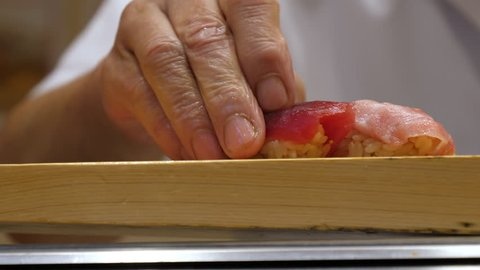 Japanese chef prepare nigiri sushi at the restaurant, close up, filmed in 4K