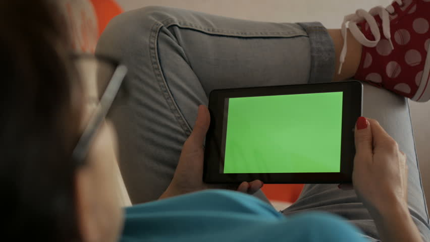 Girl using digital tablet.  Woman holding a tablet in the hands of a green screen green screen, hand of man holding mobile smart phone with chroma key green screen on white background. Technology.  #1023194647