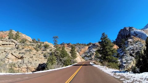 POV road trip driving rocky desert landscape vehicle motion extreme climate snow Zion National Park Utah USA