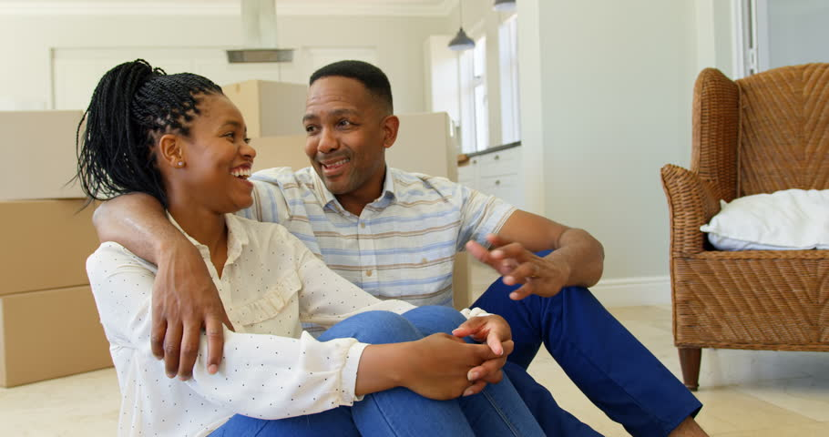 Front view of happy young African American couple sitting on floor and interacting with each other at home. African American Man pointing up by finger | Shutterstock HD Video #1023214717