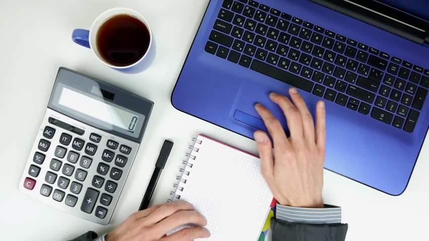 A man works with a laptop on a white table. Notepad, calculator, cup of tea, pen. Top view | Shutterstock HD Video #1023225517