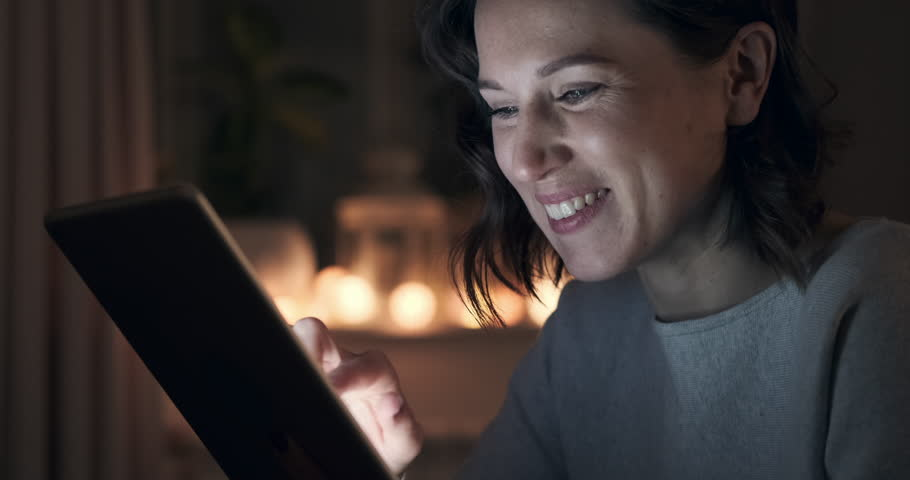 Cheerful woman using digital tablet at night | Shutterstock HD Video #1023237757