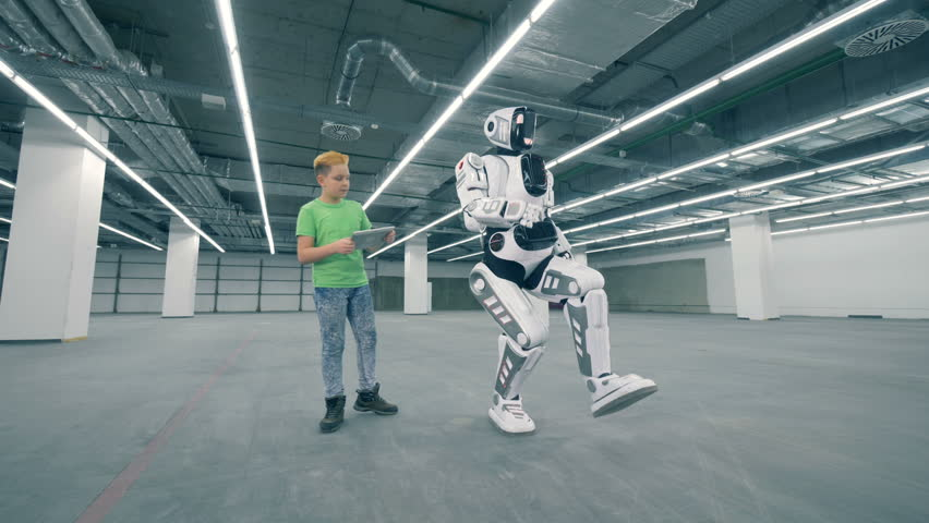 Human-like robot is moving while being guided by a kid with a tablet | Shutterstock HD Video #1023238927