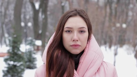 Portrait of a beautiful and smiling woman with brown hair, nodding agreement, which means yes, against a winter park or forest background. Concept of emotion