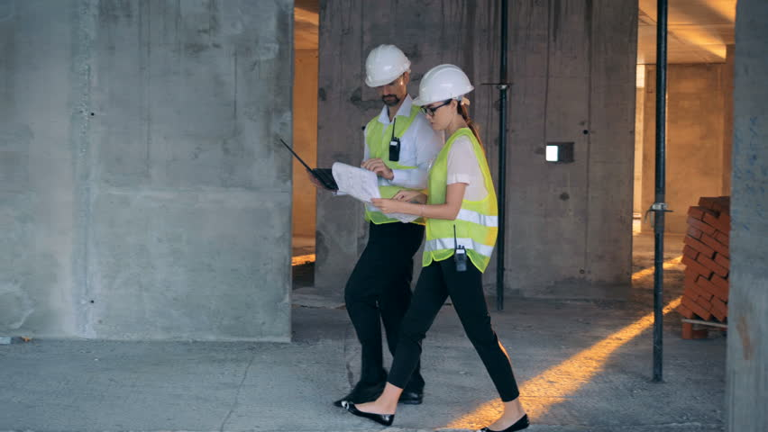 Two engineers talking while working on a construction site, side view. | Shutterstock HD Video #1023304057