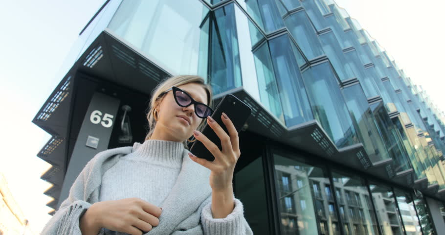 Portrait of good-looking blonde with smartphone in background of modern business center. Cute young woman wearing fashionable clothes and purple sunglasses. Good mood. Smile.