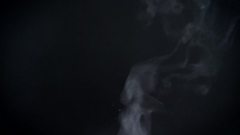 Closeup shot of vapouring smoke slowly flying on black background.