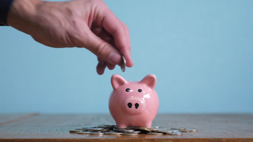 Piggy bank business standing on a pile of coins concept. A hand is putting a coin in a piggy bank on a yellow background. saving money is an investment for lifestyle the future. Banking investment and | Shutterstock HD Video #1023393757