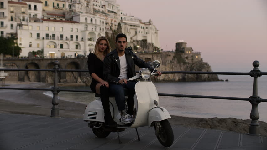 Portrait of stylish Italian couple on a scooter with view of coast with buildings and the ocean in the background, in the Amalfi Coast at sunset