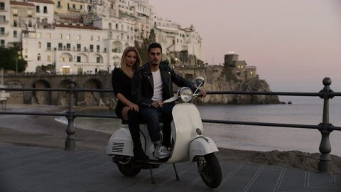 Wide to medium shot on 8k helium RED camera. Portrait of stylish Italian couple on a scooter with view of coast with buildings and the ocean in the background, in the Amalfi Coast at sunset