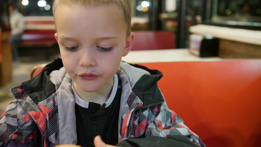 A fun shot of a cute little boy eating french fries and a hamburger for dinner at a restaurant | Shutterstock HD Video #1023401497