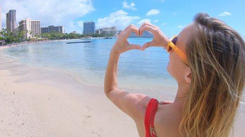 Young woman on Waikiki beach in Hawaii making a heart shape finger frame. Romantic woman putting her hands together to for a heart shape frame with her hands on the beach in Hawaii