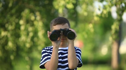 Little boy walking in the park and looking through binoculars